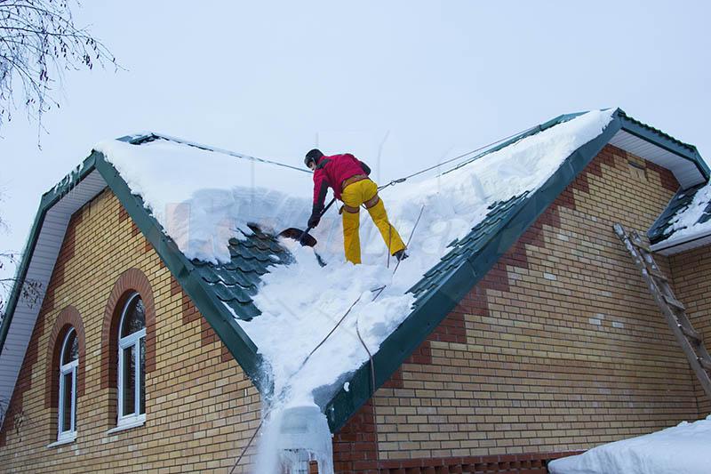 Очистка крыши дома от снега альпинистами